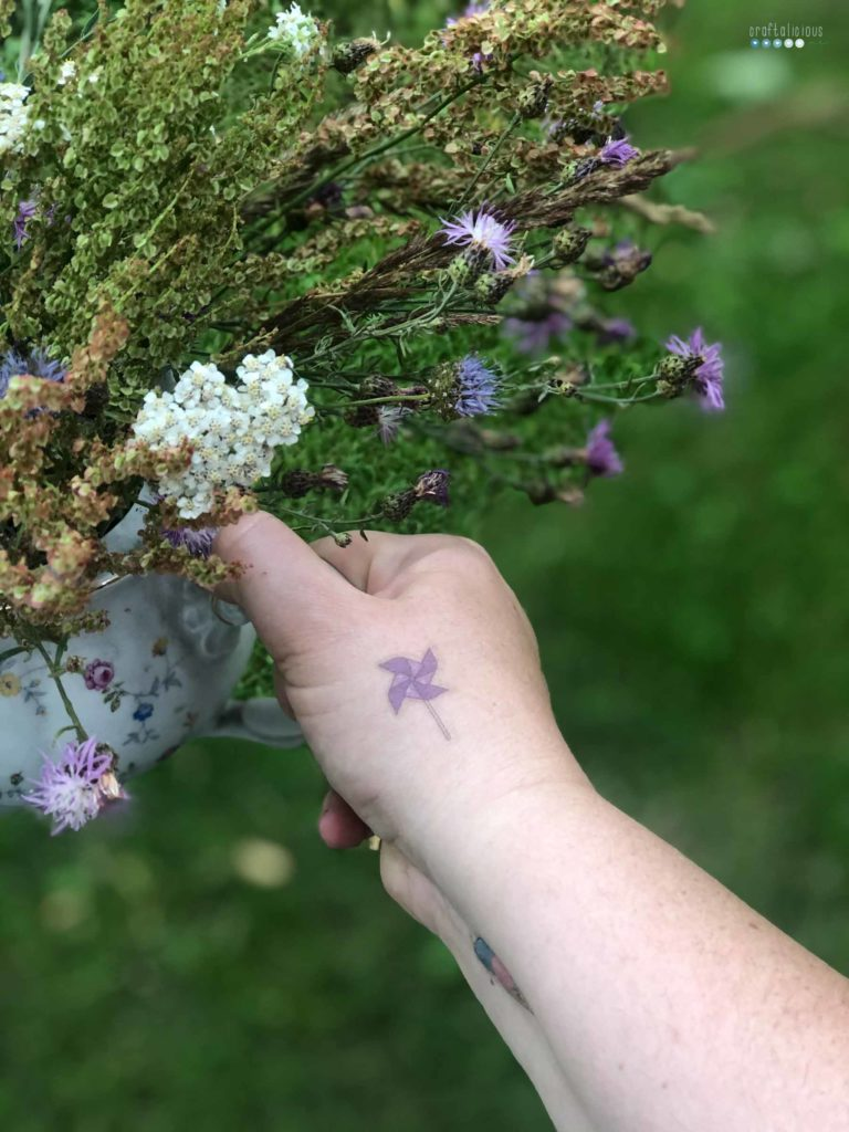 enjoying summer at home with summer flowers from the meadow in an old coffee put while wearing temporary tattoos